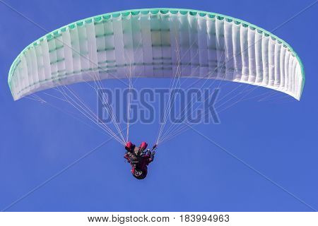 Paragliding in tandem extreme sport free gliding and blue sky as background