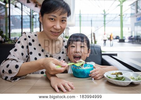 Asian Chinese Mother And Daughter Eating Beef Noodles