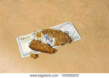 One hundred dollar bill and piece of bread on a top studio closeup