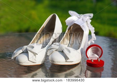 White shoes the bride's garter and wedding rings in red box. Soft focus selective focus