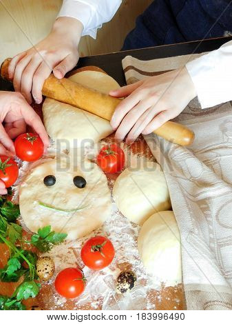 Yeast dough with a funny face and a baker forming dough surrounded by tomatoes, fresh green, quail eggs and olives