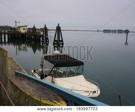Fishing boat docked at marina with small dock structure in the distance
