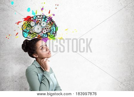Side view of an African American woman wearing a green shirt standing near a concrete wall with a colorful brains sketch and cogs on it. Mock up