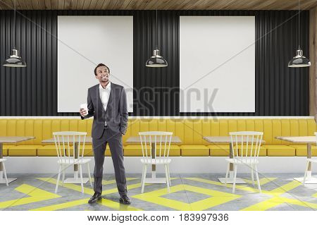 African American businessman standing in a cafe with posters hanging on a black wooden wall yellow sofa square tables and white chairs near them. 3d rendering mock up