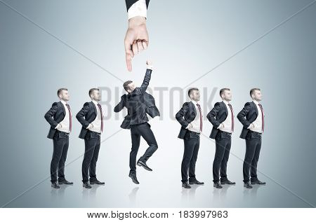 Row of businessmen candidates for a good vacancy is standing against a gray background. A hand is pointing on one of them. He is jumping triumphantly.