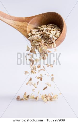 Spoon Of Oatmeal Falling On A White Background