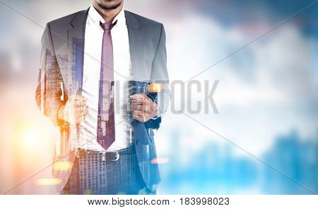 Close up of an African American businessman wearing a suit and a red tie and standing against a blurred city panorama. Mock up toned image double exposure