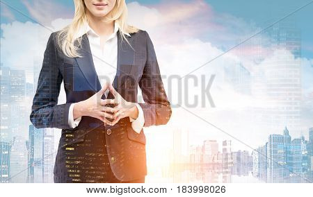 Close up of an unrecognizable blond businesswoman in a suit standing against a morning city panorama. Mock up toned image double exposure
