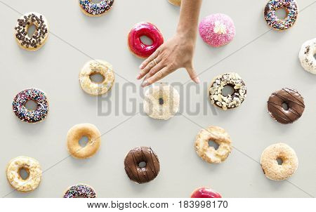 Hands selecting a variety of donut flavour