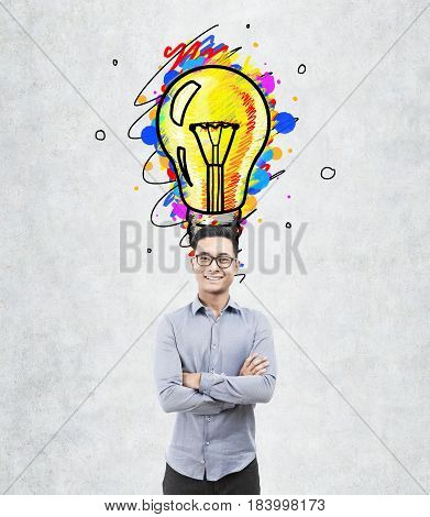 Portrait of a happy Asian businessman in glasses standing with crossed arms near a concrete wall with a large light bulb sketch