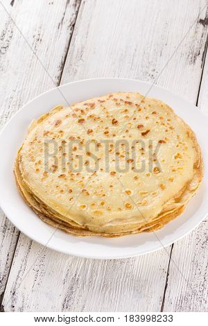 Thin Pancakes On A White Plate. Maslenitsa. Russian Pancakes On A Light Wooden Background. In A Rust