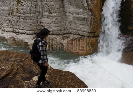 Traveler girl walking in waterfall canyon. Travel adventure and hiking activity active and healthy lifestyle on summer vacation and weekend tour