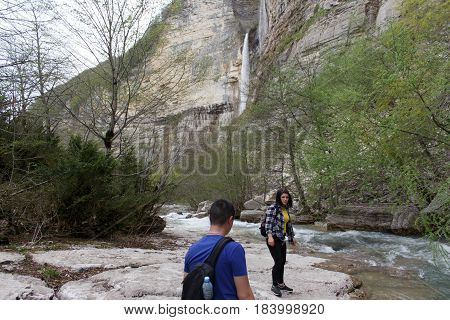 Traveler young girl and men walking in waterfall canyon. Travel adventure and hiking activity. Travel adventure and hiking activity active and healthy lifestyle on summer vacation and weekend tour