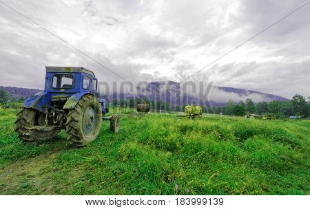 Altai Mountains, the vicinity of a small village. An old tractor in the meadow.