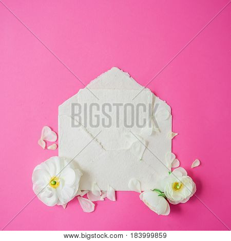 White flowers, petals and paper envelope on pink background. Flat lay, top view. Vintage background.