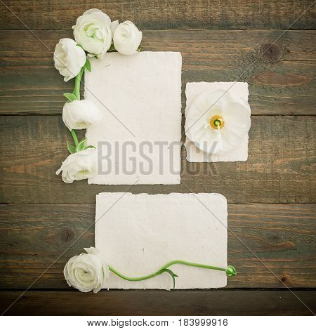Paper cards, envelope and white flowers on wood background. Flat lay, top view. Vintage background.
