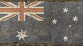 Old grunge vintage dirty faded shabby distressed Commonwealth of Australia national flag background on broken concrete wall with cracks poster