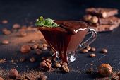 Homemade hazelnut spread or hot chocolate in glass bowl with nuts and chocolate bar. Cocoa powder nuts and chocolate background. Ingredients for cooking homemade chocolate sweets. poster