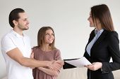 Portrait of happy smiling couple and real estate broker shaking hands, young family meeting with banker to discuss mortgage loan, female advisor handshaking clients, visiting notary office poster