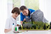 Father and son work on model building school project. Kids and parent build miniature scale model mountain for geography class. Extracurricular activities and family hobby. Art and crafts for child. poster