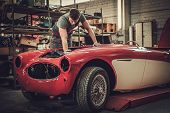 Mechanic working on classic car electrics in restoration workshop poster