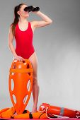 Accident prevention and water rescue. Attractive female model in lifeguard outfit on duty looking through binocular keeping float lifesaver equipment on gray poster
