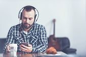 Finding inspiration in music . Involved thoughtful professional musician sitting in the studio and using smartphone and earphones while listening to the music poster
