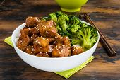 Chicken lacquered with a sweet soy teriyaki sauce in a white bowl. Garnished with rice and broccoli. Chopsticks brown wooden table. poster