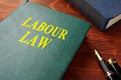 Book with title labour law on a wooden surface. poster
