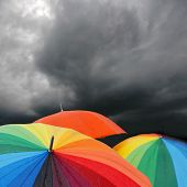 Rainbow Umbrellas Under Storm Clouds