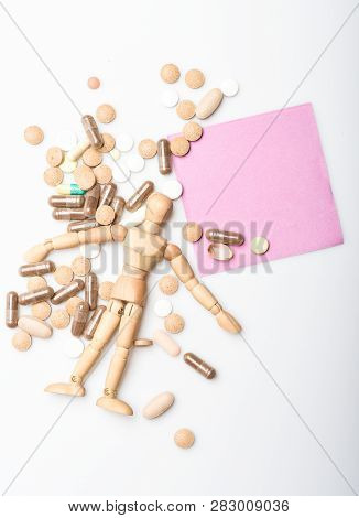 Health and treatment. Health care and problems. Immunity and medicine vitamins. Overdose and death. Medicine prescription. Wooden human dummy lay on pile of pills and tablets. Take medicine concept poster