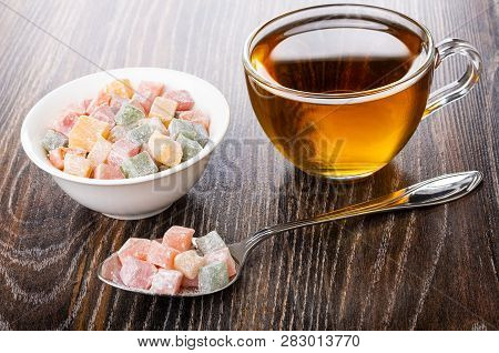 Cubes Of Multicolor Rakhat-lukum In Spoon, Bowl With Rakhat-lukum, Cup Of Tea On Dark Wooden Table