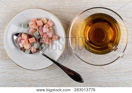 Cubes Of Multicolor Rakhat-lukum, Spoon In White Saucer, Cup Of Tea On Saucer On Wooden Table. Top V