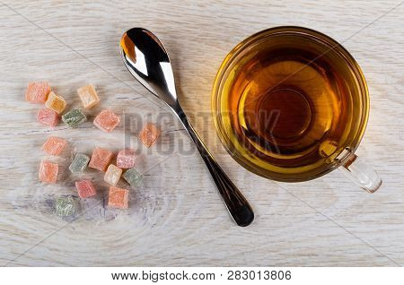 Scattered Multicolor Rakhat-lukum, Cup Of Tea, Teaspoon On Wooden Table. Top View