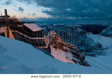 Panoramic View Of Beautiful Snowy Zugspitze Mountains On Sunset. Summit. Bavarian Alps, Germany