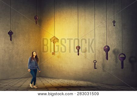 Confident Young Woman Walking In A Dark Room To Find The Magic Key To Success. Concept Of Business A