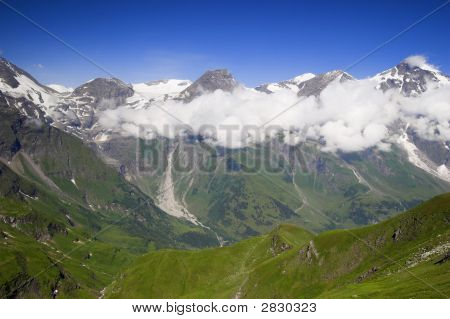 High Mountain View With Clouds And Frosen Snow