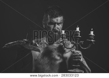 Magic Spell, Enchantment, Witchcraft. Hipster Man With Book And Candles Burning On Purple Background