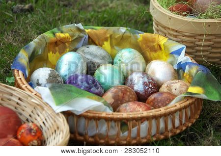 Painted Eggs At Easter. Easter Eggs In Basket On Green Grass.