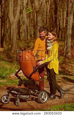 Woman And Man Walk With Baby Pram In Park, Happy Relations. Family Relations. Sharing Quality Time T