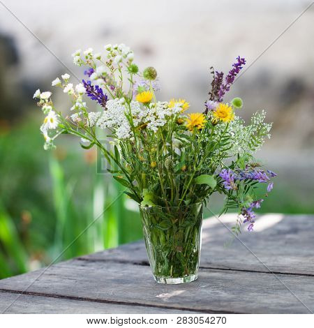 Beautiful Bouquet Of Bright Wildflowers In A Glass. Vintage Wooden Table Background.