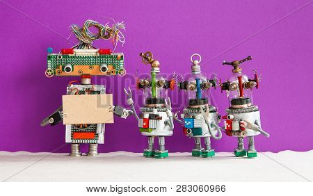 Robot With A Cardboard Mockup And Four Funny Robotic Toys On Purple Wall Background. Copy Space For
