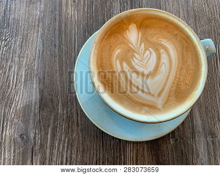 A Cup Of Cafe Latte On A Wooden Table.