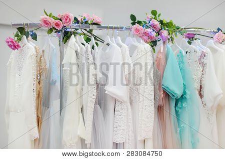 Few Beautiful Wedding, Bridesmaid Or Evening Dresses Ball Gown On A Hanger In A Bridal Shop. Wedding