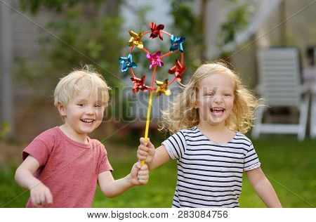 Little Boy And Girl Having Fun During Walk. Happy Child With Pinwheel. Preschoolers Or Toddlers Birt