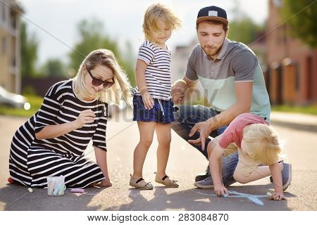 Happy Amicable Family With Two Children Walking In Summer. The Word