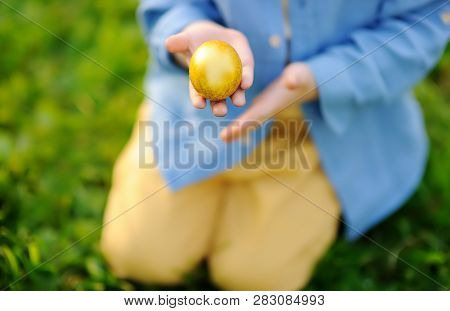 Close-up Photo Of Little Boy Hunting For Easter Egg In Spring Park On Easter Day. Cute Little Child