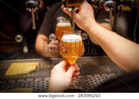 Close-up of barman hand at beer tap pouring draught craft beer poster