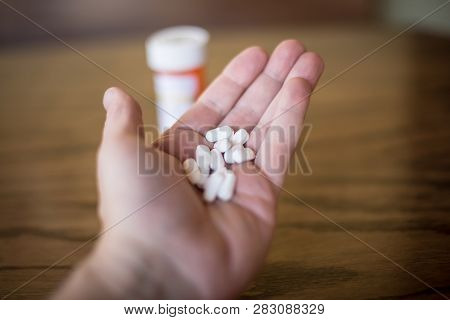 Holding Handful Of Opioid Painkillers In Front Of Orange Prescription Bottle