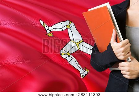 Learning Language Concept. Young Woman Standing With The Isle Of Man Flag In The Background. Teacher